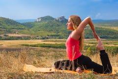 美丽的亭亭玉立的妇女做瑜伽鸠姿势 库存照片