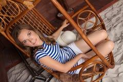 美丽的亭亭玉立的妇女坐在海滩的木摇摆 免版税库存照片