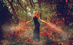 美丽的亭亭玉立的红头发人巫婆在森林召唤 图库摄影