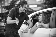 美丽的人民互相谈话在街道在汽车附近 免版税库存照片