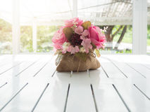 美丽的人造花花束在白色木桌上的 免版税库存照片