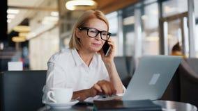 美丽的企业夫人谈话在手机和与在咖啡馆的膝上型计算机一起使用 影视素材