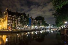 美丽的传统老大厦在沿运河的晚上有在水的反射的在阿姆斯特丹,荷兰 库存照片