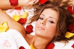 美丽的位于的瓣玫瑰色妇女年轻人 免版税库存照片