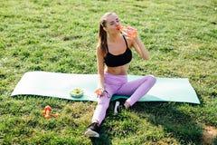 美丽的体育女孩在公园吃沙拉和饮用水 库存图片