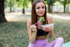 美丽的体育女孩在公园吃沙拉 库存图片