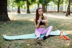 美丽的体育女孩在公园吃沙拉 图库摄影
