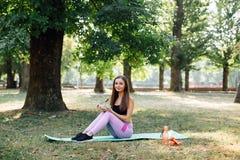 美丽的体育女孩在公园吃沙拉 库存照片