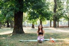 美丽的体育女孩在公园吃沙拉 免版税图库摄影