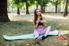 美丽的体育女孩在公园吃沙拉 免版税库存图片
