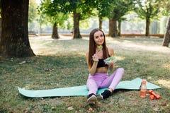 美丽的体育女孩在公园吃沙拉 免版税库存照片
