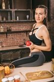 美丽的体育妇女在她的手上坐厨房用桌用一个苹果 体育营养饮食和卡路里计数 库存照片