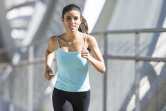 年轻美丽的体育运动妇女运行的和跑步的横渡的现代金属城市桥梁 库存照片