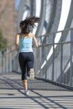 年轻美丽的体育运动妇女运行的和跑步的横渡的现代金属城市桥梁 免版税图库摄影
