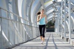年轻美丽的体育运动妇女运行的和跑步的横渡的现代金属城市桥梁 库存图片