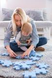 美丽的使用与难题片断的妇女和她的婴孩,当坐一张地毯在客厅时 免版税库存照片