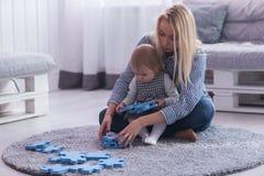 美丽的使用与难题片断的妇女和她的婴孩 免版税库存照片