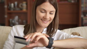 美丽的使用在家在网上购物与信用卡生活方式的smartwatch的妇女网路银行 股票视频