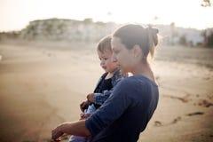 美丽的使用在海滩的母亲和儿子 库存图片