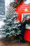 美丽的俄国女孩在冬季衣服的一云彩天获得乐趣在Tverskaya广场及时圣诞节打过工 免版税库存图片