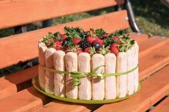 美丽的假日蛋糕用木表面上的夏天莓果在小修道院 免版税库存照片