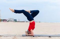 美丽的做体育的年轻人适合的妇女行使,支持的headstand姿势, salamba sirsasana,侧视图的变异 免版税图库摄影