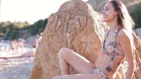 美丽的健康妇女画象有适合的身体的在时尚性感的比基尼泳装 式样摆在由在光芒的海岩石  股票视频