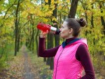 美丽的健身体育女孩在运动服的秋天公园喝水或能量饮料从体育瓶 免版税库存图片