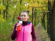 美丽的健身体育女孩在运动服的秋天公园喝水或能量饮料从体育瓶 库存照片