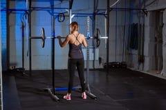 美丽的健身妇女举的杠铃 运动的妇女举的重量 行使大厦肌肉的适合的女孩 健身和 免版税库存照片