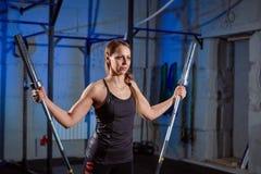 美丽的健身妇女举的杠铃 运动的妇女举的重量 行使大厦肌肉的适合的女孩 健身和 免版税库存图片