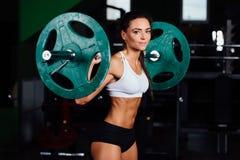 美丽的健身妇女举的杠铃 免版税库存照片