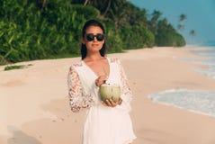 美丽的光亮的年轻人晒黑了戴一件白色衬衣和时尚太阳镜的海滩的女孩,拿着一个新鲜的椰子 库存照片