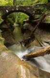 美丽的光滑的流动的小河在Hocking小山国家公园,俄亥俄的一座石桥梁下 免版税库存图片