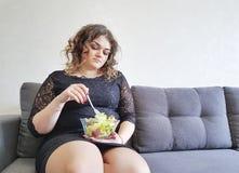 美丽的全长在有沙拉板材的长沙发压下的女孩坐的生活方式  免版税图库摄影