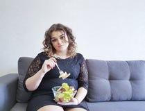 美丽的全长在长沙发的女孩坐的生活方式有沙拉板材的  图库摄影