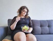 美丽的全长在长沙发的女孩坐的生活方式莴苣有沙拉板材的  免版税库存图片