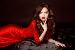 美丽的典雅的深色的妇女式样佩带在时尚红色博士 免版税库存图片