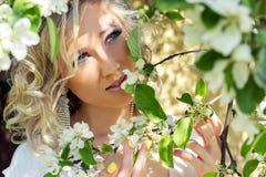 年轻美丽的典雅,可爱的女孩站立在森林里的在与长的头发的开花的树附近白肤金发在晴天和构成 免版税库存图片
