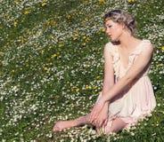 年轻美丽的典雅,可爱的女孩站立在森林里的在与长的头发的开花的树附近白肤金发在晴天和构成 免版税库存照片