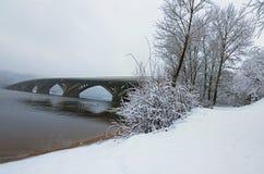 美丽的冬天风景照片 在Dnipro河反映的Metrosubway桥梁 雪盖树` s早午餐和地面 免版税库存照片