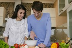 美丽的准备早餐的女孩和男孩在厨房里 免版税库存图片