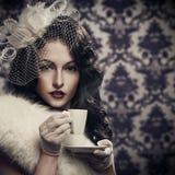 美丽的减速火箭的夫人饮用的咖啡 库存照片