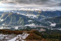 美丽的剧烈的多雪的高加索山脉在河谷锐化与滑雪吊车、倾斜和一个村庄的冬天风景 免版税库存图片