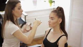 美丽的化妆师应用唇膏 构成大师,年轻秀丽红头发人模型的绘的嘴唇的手 ?? 股票视频