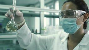 美丽的化验员剥离有化学制品流体的烧瓶 影视素材