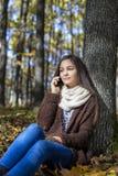 美丽的十几岁的女孩和讲话坐电话 库存照片