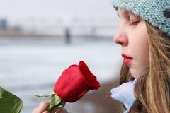 美丽的十几岁的女孩嗅室外红色的玫瑰 特写镜头po 库存图片