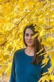 美丽的十几岁的女孩在与黄色叶子的树下在秋天 免版税库存图片