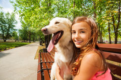 美丽的十几岁的女孩坐并且拥抱她的狗 免版税库存照片